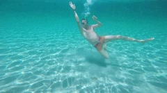 Underwater view of a tourist, swimming in the tropical clear sea Stock Footage