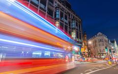 LONDON - JUNE 14, 2015: Red Double Decker Bus speeds up in city streets at ni Kuvituskuvat