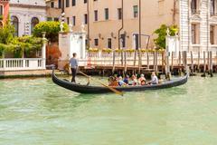 Venice. The boat trip tourists in gondolas. - stock photo