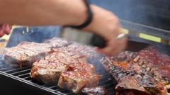 A man barbecues huge ribs and steak for summer party Stock Footage