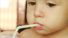 Pretty face of little blonde girl drinking juice with straw Stock Footage