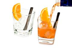 Barman pouring spritz aperitif aperol cocktail in two glasses with orange sli Stock Photos