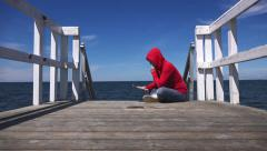 Young woman in red shirt reading at ocean pier Stock Footage