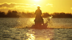 Cowboy Camargue rider animal horse sunrise galloping water Stock Footage