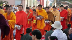 Many people give food and drink for alms to 10000 Buddhist monks - stock footage