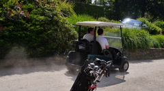Two men driving by with a golf car Stock Footage