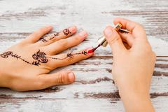 Woman Hands Painted with Black Henna Polishing the Nails - stock photo