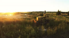Girl sitting on the dozer in a quarry. Aerial view. Camera around Stock Footage