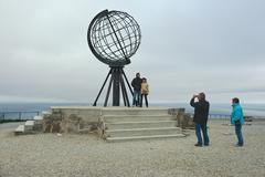 People make photo with symbolic globe at North Cape, Norway. - stock photo