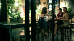 Friends sitting in the pub and invite someone, steadycam shot Stock Footage