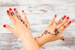 Woman Hand Painted with Floral Figures Using Black Henna - stock photo