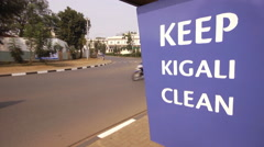 'Keep Kigali Clean' sign with cars, motorbikes, motorcycles driving past on a Stock Footage