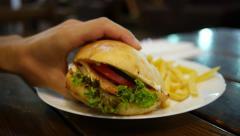 Man eat tasty big burger in a fast food restaurant closeup Stock Footage