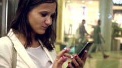 Beautiful smiles businesswoman uses mobile phone inside an elevator while moving Stock Footage