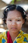 A girl wears traditional Thanaka on her face at her family's small snack shop Stock Photos