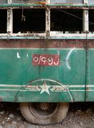 Side view of a dilapidated vintage green bus in Burma. Window glass has gone Stock Photos