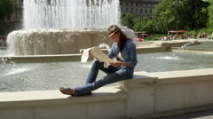 Woman looking on the map next to the fountain, steadycam shot Stock Footage