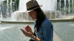Woman using smartphone next to the fountain, steadycam shot Stock Footage
