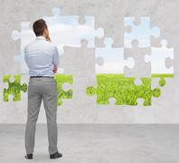 Businessman over puzzle with natural landscape Kuvituskuvat