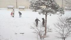 Stock Video Footage of Children playing at school yard and the flaky snow is falling down