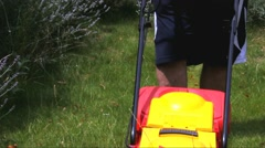 Man moves with lawnmower and  mows green grass Stock Footage