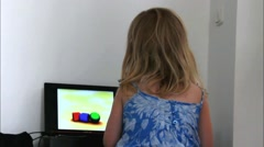 Adorable blonde toddler girl looking cartoon on laptop - stock footage