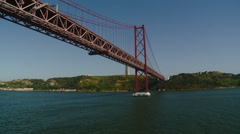 Portugal - Passing under 25th of April Bridge with Statue of Christ in Backgr Stock Footage