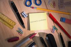Distance learning against students table with school supplies Stock Photos