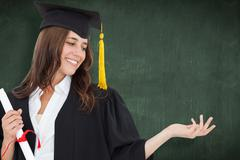 Stock Photo of Composite image of a smiling woman with a degree as she opens out her other hand