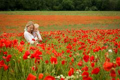 Mommy and daughter in a meadow - stock photo