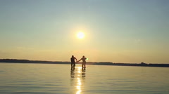 Two happy homosexual running on water at sunset - stock footage