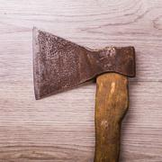 Old and dirty axe on wood background - stock photo