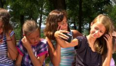 Children sitting on bench and using cell phones, slow motion, pan right, leisure - stock footage
