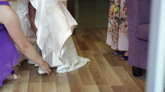 Bridesmaid helps the bride to wear shoes Stock Footage