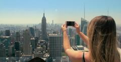 Woman taking picture with smartphone of New York City skyline. Stock Footage