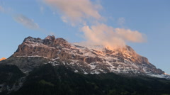 Swiss Grindelwald Eiger mountain sky clouds snow rugged outdoor sport time lapse Stock Footage