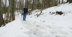 Man walking up snow covered trail - stock footage