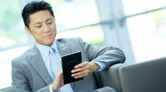Asian Chinese businessman using touch screen mini tablet in the office - stock footage