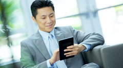 Male Asian Chinese financial advisor working with wireless tablet Stock Footage