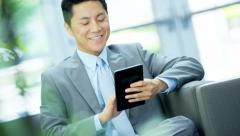 Portrait of Asian Chinese businessman using touch screen tablet in office Stock Footage