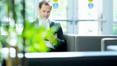 Caucasian American business consultant in the city atrium with wireless tablet - stock footage