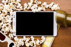 Tablet pc on wood with attributes of cinema - stock photo