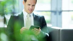 Male Caucasian financial insurance advisor working with wireless tablet device - stock footage