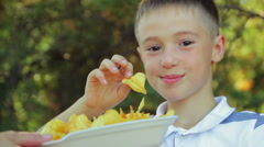 The little boy close-up eats golden chips in the park on nature, fast food Stock Footage