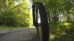 Bicycle wheel in motion POV bike ride through forest Arkistovideo