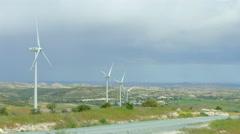 Beautiful pan of summer field, green hills, wind farm generating electricity Stock Footage