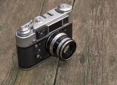 retro the camera on an old wooden table - stock photo