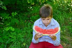 Teen boy eating watermelon in  nature - stock photo