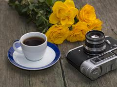 bouquet of yellow roses, cup of coffee and a retro the camera on a table - stock photo