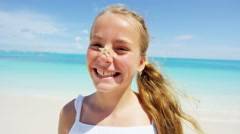Smiling portrait of a blonde Caucasian girl outdoors on a beach - stock footage